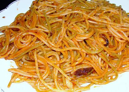 Hotové špagety smíchané se směsí na talíři